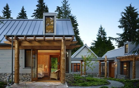 Three farmhouses in sheet-like metal panel roofing with 2 flat roof dormers, a rustic exterior design, and an outdoor landscape.