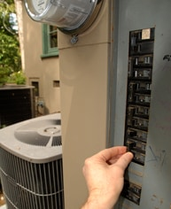 Hand switching off an outdoor circuit breaker with a central AC compressor in the background.