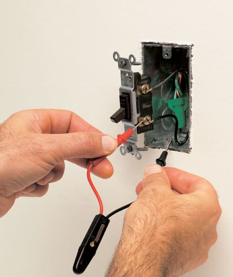 Man's hands holding a neon tester's insulated parts including a red probe tip touching a brass terminal screw and a black probe tip meeting a metal box screw hole.