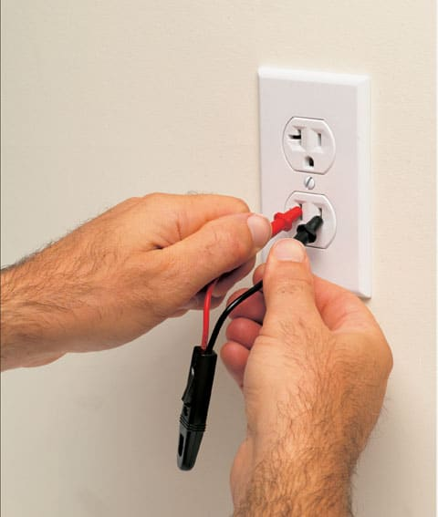 Man's hands holding a neon tester's insulated parts with red and black probe needle-tips inserted inside the slots of a T-shaped power outlet.