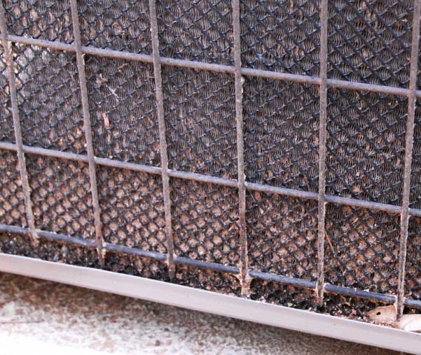 The outer portion of a central air conditioner's coils, caked with dirt.
