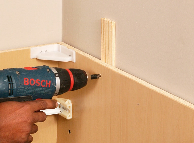 Screw through backs of cabinets and shims into wall studs.