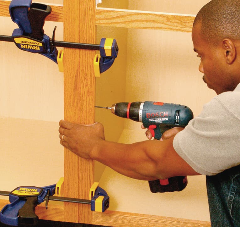 Clamp together adjoining cabinets, and then screw through the edge of one face frame into the other.