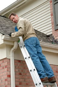 Man looking behind while standing on a step ladder, leaning on a rain gutter.