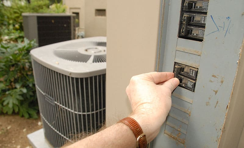 Hand turning off an outdoor circuit breaker next to a central air conditioner compressor.