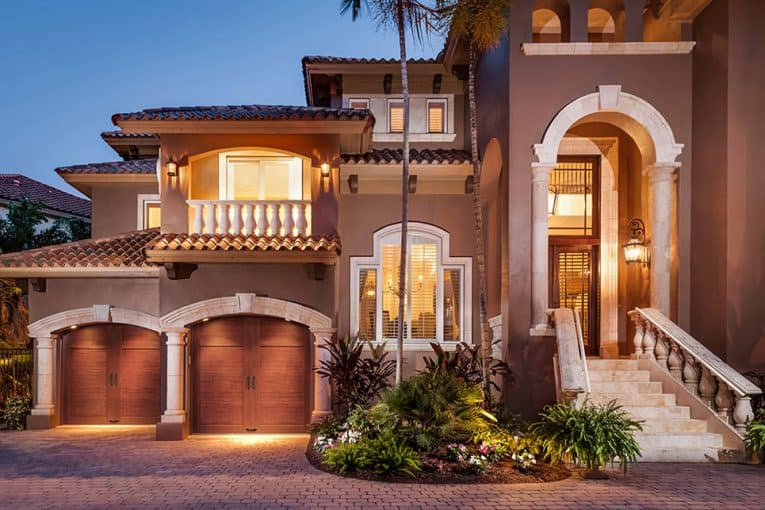 Two-story Mediterranean house's front yard including an outdoor landscape and a carriage-style, wooden double door garage.