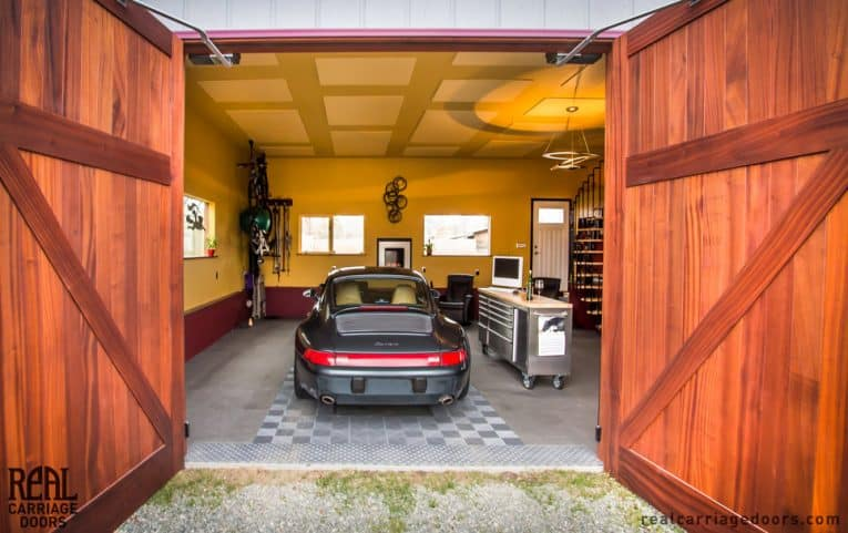 Open solid-wood doors in a swing-out carriage garage including a sports car, a stainless metal tool cabinet with a monitor on top, an armchair, a pendant ceiling light, and a spiral staircase.
