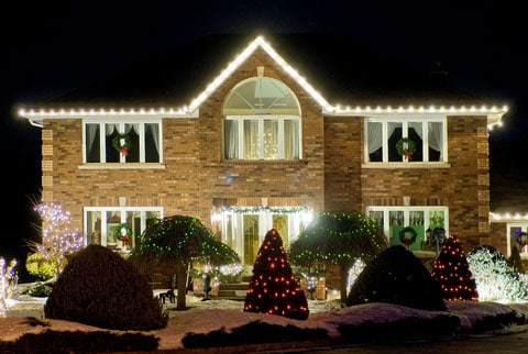 Two story brick house at night, with Christmas lights on the roofline and in the garden.