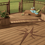Outdoor two-level composite deck with railings including planter boxes with flowers and a wicker chaise lounge.