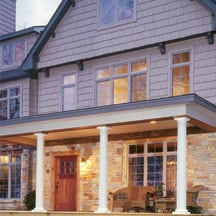 Stately wooden columns support the roof of this front porch.