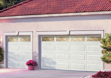 White steel double door garage with raised panel design and gold decorative window frames including a pot of pink flowers.