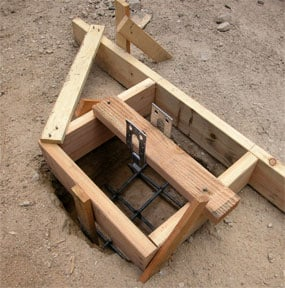 Square concrete pier mold made of lumber scraps including a reinforcing bar under and side supports.