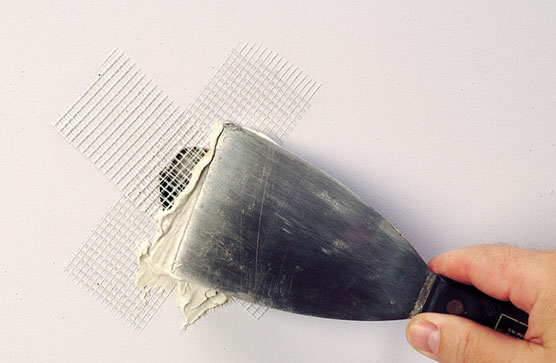 Patching hole in drywall by applying spackling compound over fiberglass mesh tape