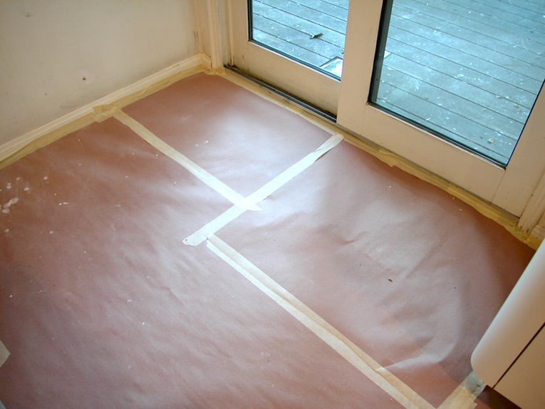 Masking tape does double duty, masking trim and keeping paper drop cloth in place during painting.