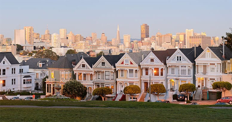 Classic Victorian houses stand proudly against a San Francisco backdrop.