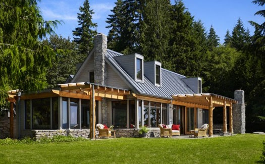 A modern forest home with grey standing seam metal roof.