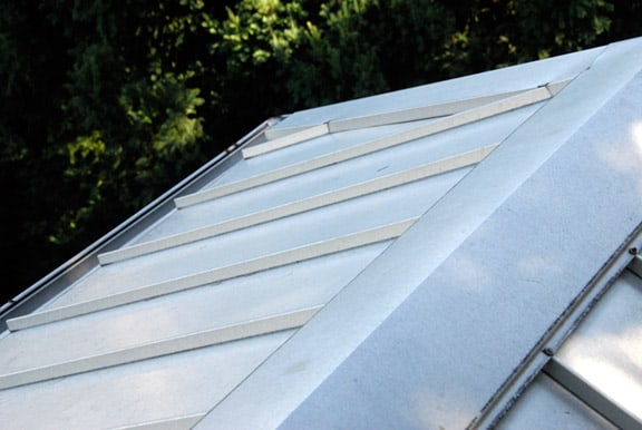 An installed section of light grey sheet metal roofing.