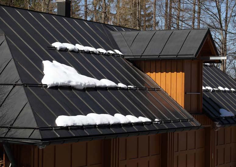 A black sheet metal roof with lines of snow.