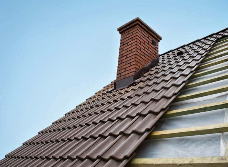 Brown metal shingles roofing over wooden battens including a brick chimney.