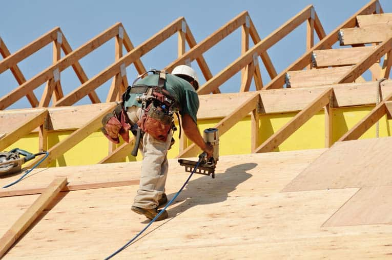 Carpenters nail plywood sheathing to the roof rafters—in this case, a series of roof trusses.