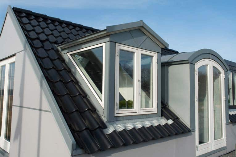 Black tile-like metal roofing including a gable window, and gray gabled and segmental dormers.
