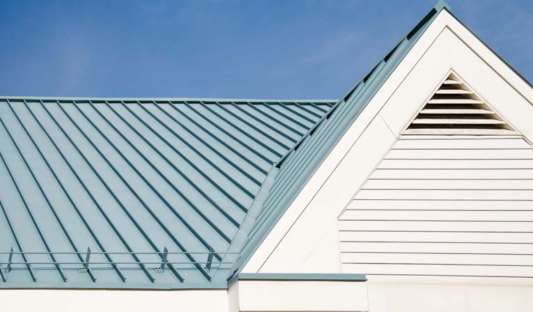 Light blue standing seam metal roofing including white triangular gable roof vent.