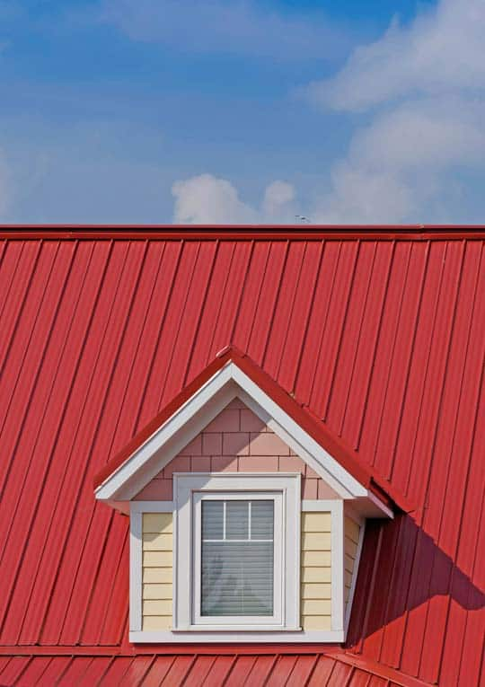 Red standing-seam metal roofing including a gabled dormer.