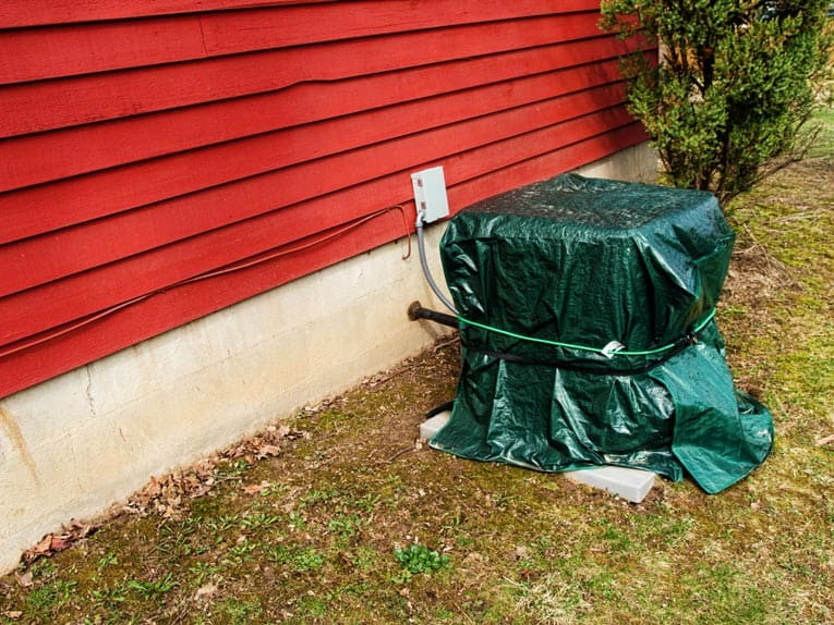 Outdoor air compressor covered in a tarp and secured with a bungee cord.