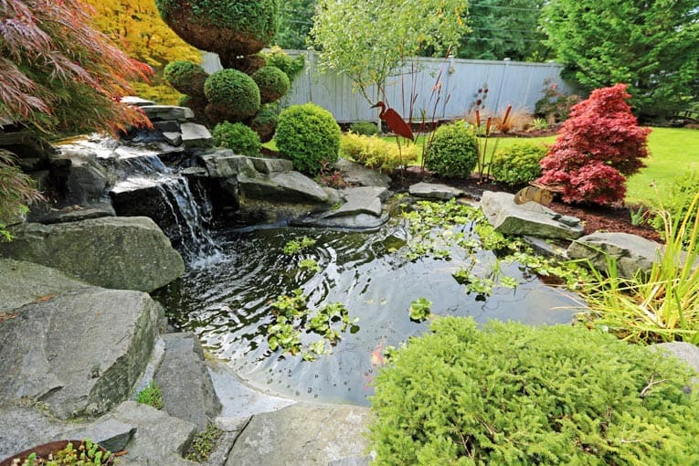 Garden pond and waterfall add beauty and tranquility to this backyard.