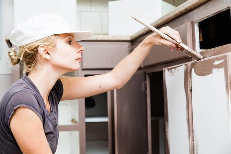 woman using paint brush to paint cabinet door