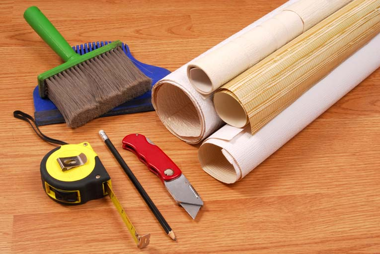 wallpapering tools on table, including brush, tape measure, pencil, and utility knife