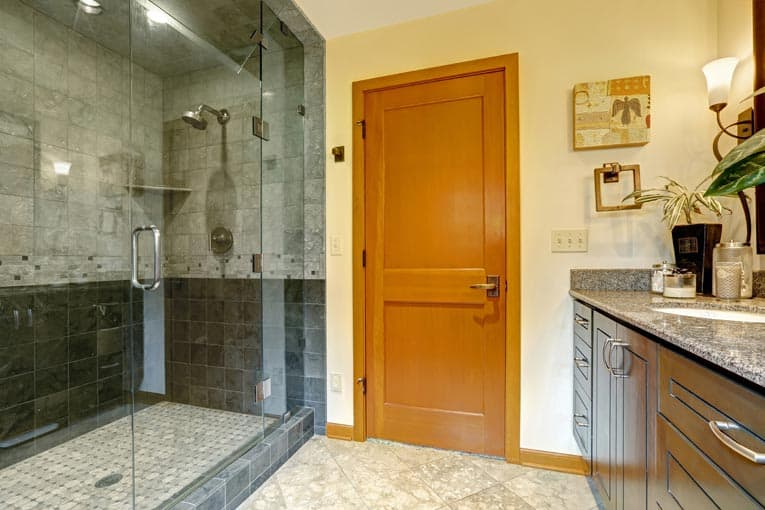 Steam shower is enclosed by floor-to-ceiling tempered glass wall and door.