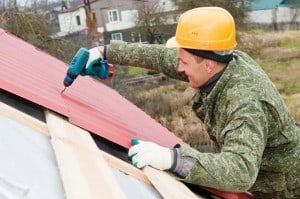 Man screwing metal roof panels over wooden battens.