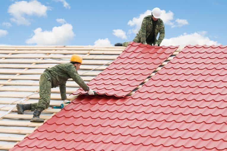 Two men installing a red metal roofing over wooden battens.