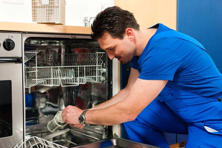 A man removing an internal part of a dishwasher.