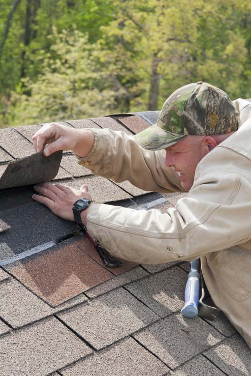 Man lifting damaged asphalt shingle at top of roof to replace it