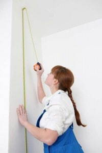 woman in overalls measuring the height of your walls with a tape measure