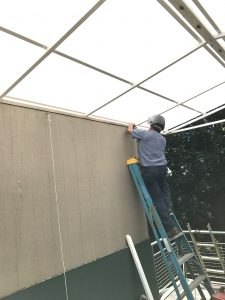 A man standing on a step ladder, anchoring a steel and polycarbonate patio roof.