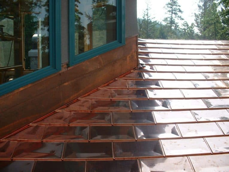 Copper shingles roofing beside a dormer window.