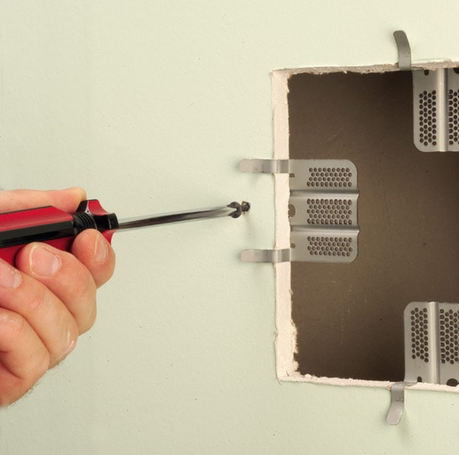 Using screwdriver to fasten drywall repair clips to four sides of cutout in drywall