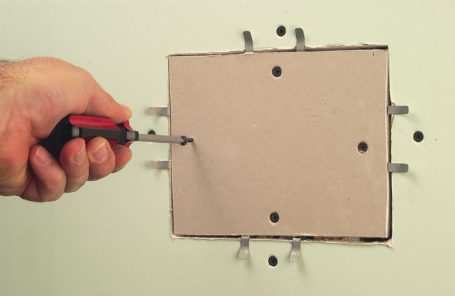 Screwing a rectangular patch of drywall to the special repair clips