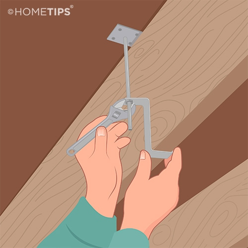 Hands using a wrench to tighten the nut on a Squeak-Ender device between the subfloor and a joist.